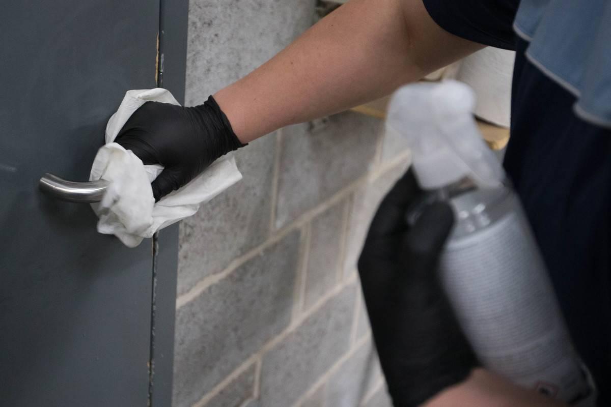 A person cleans a doorknob.