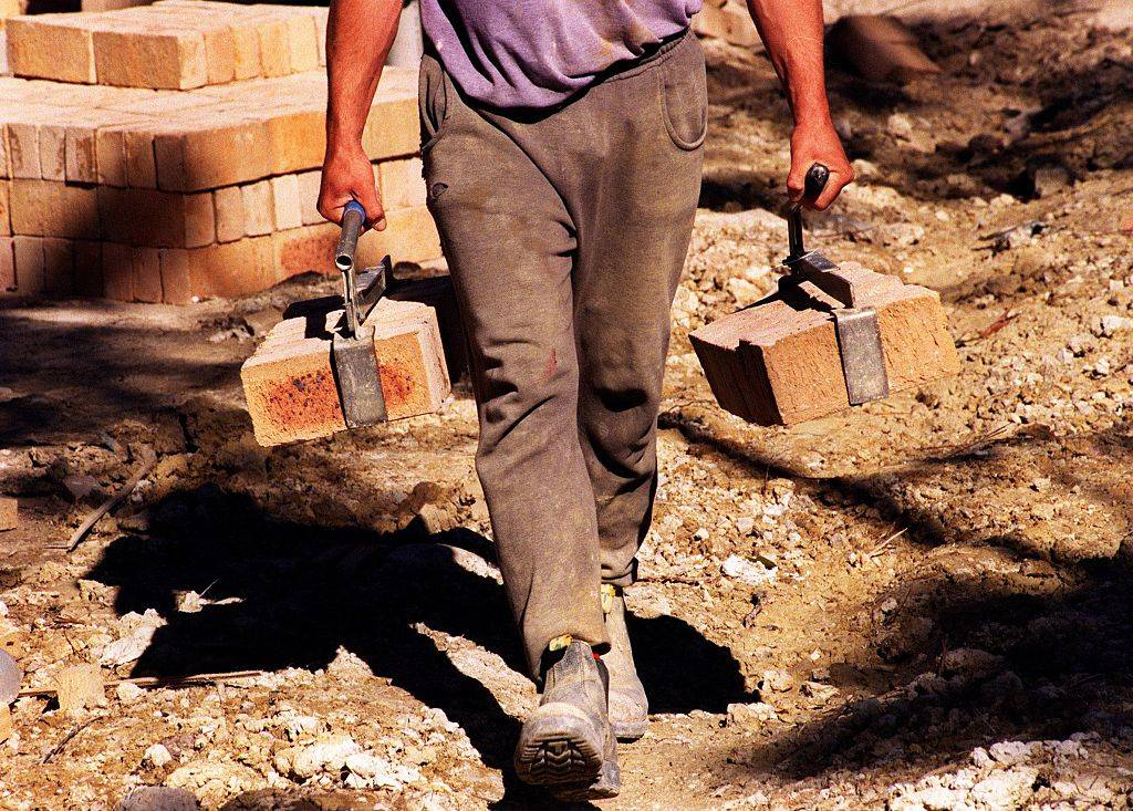 A brickie carries bricks on a house building site.