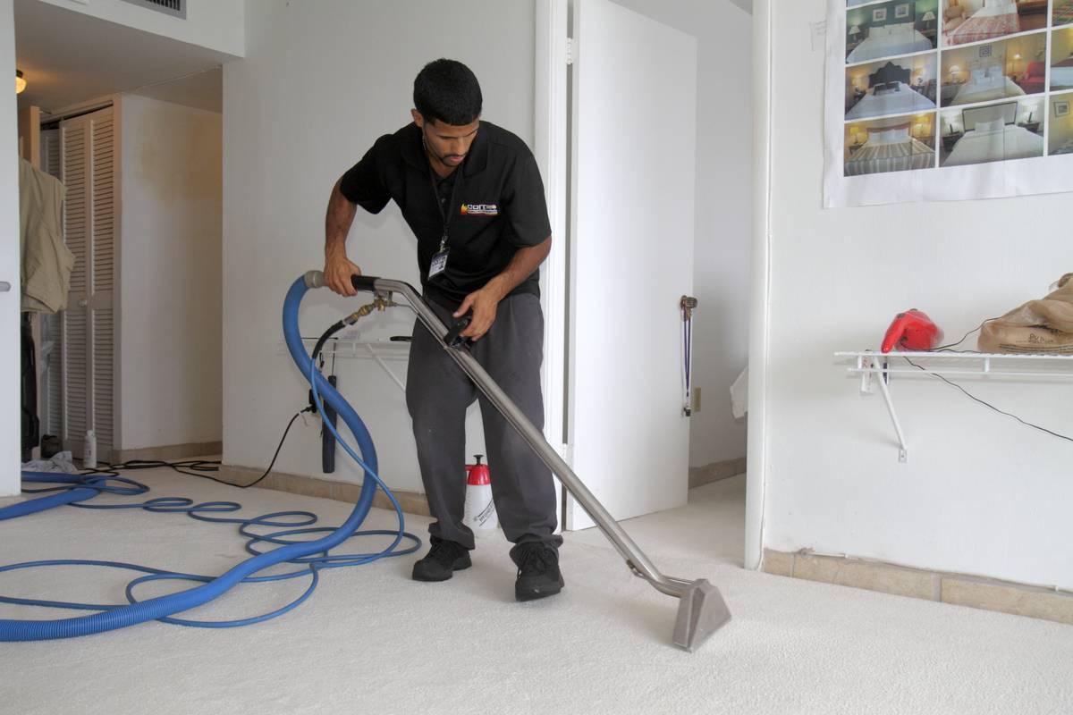 A man vacuums his carpet.