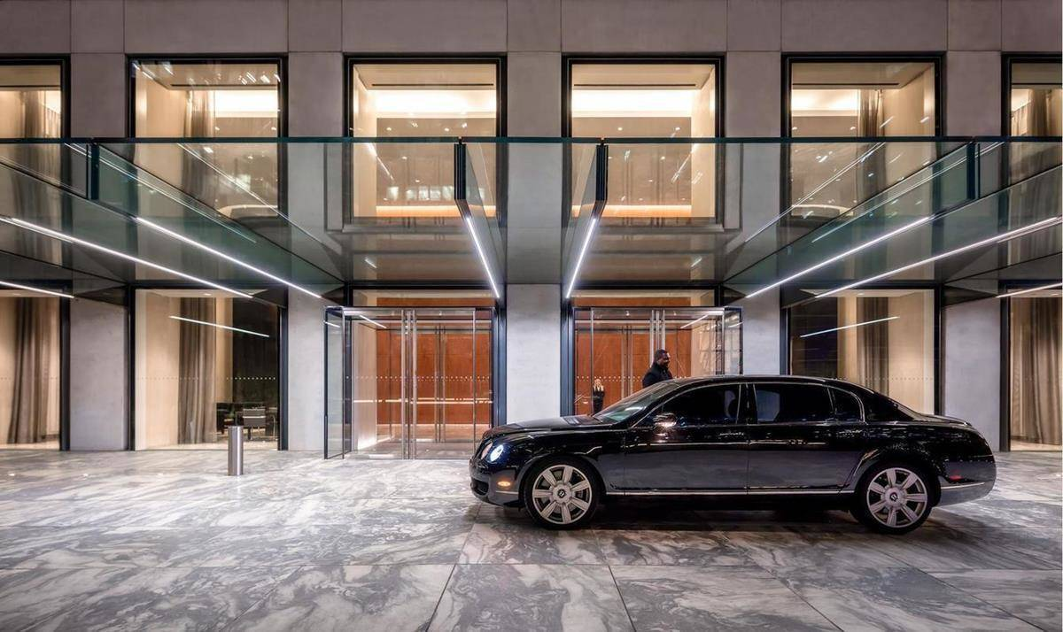 A doorman assists the driver of a luxury vehicle as they pull up to the building's entrance.