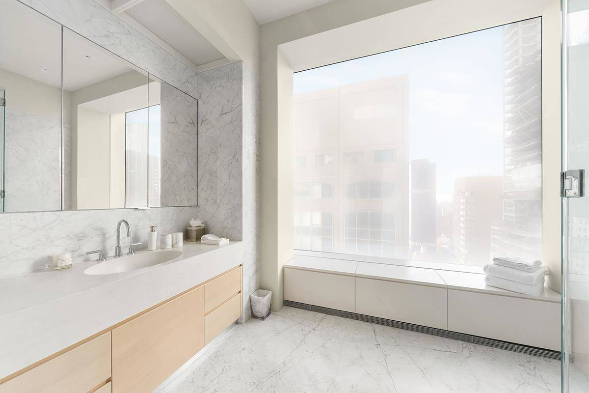 A large, square-shaped master bathroom looks out to the city.