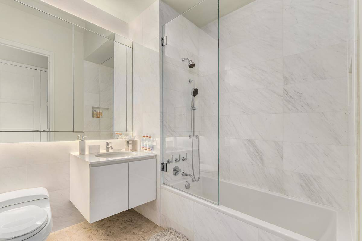 A white bathroom leads to the next bedroom.