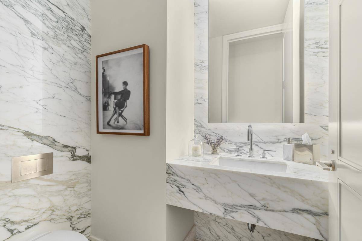 A black and white photo hangs in a marbel bathroom.