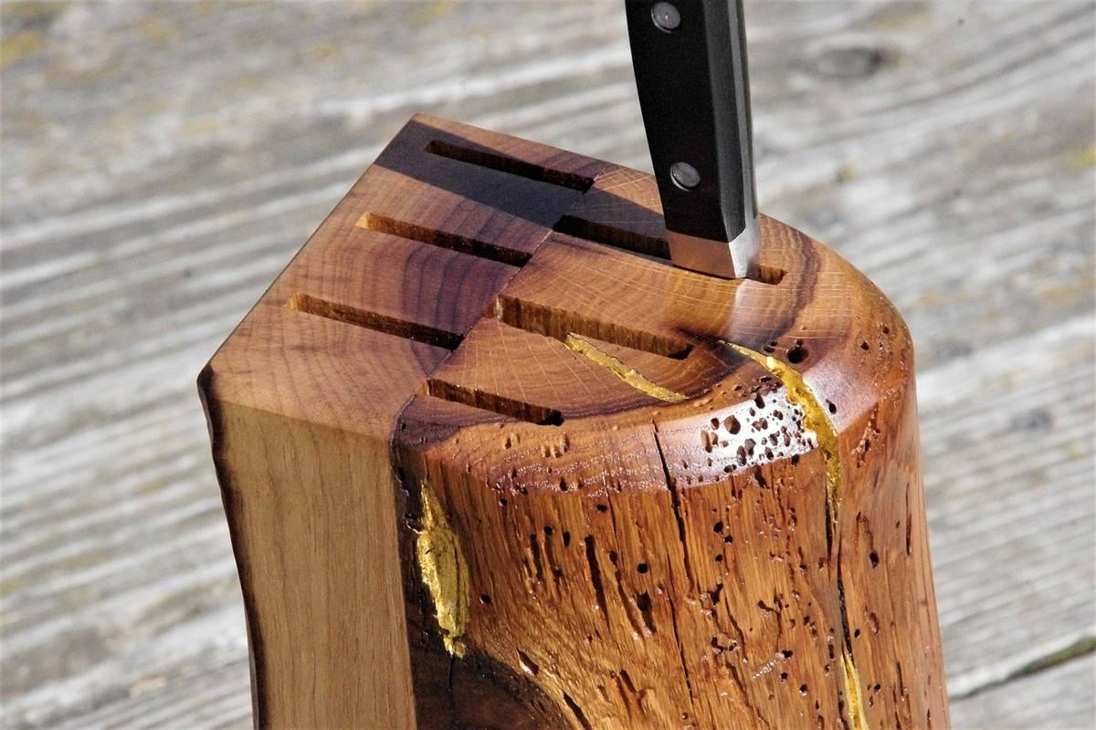 A single knife handle sticks out of a wooden knife block.