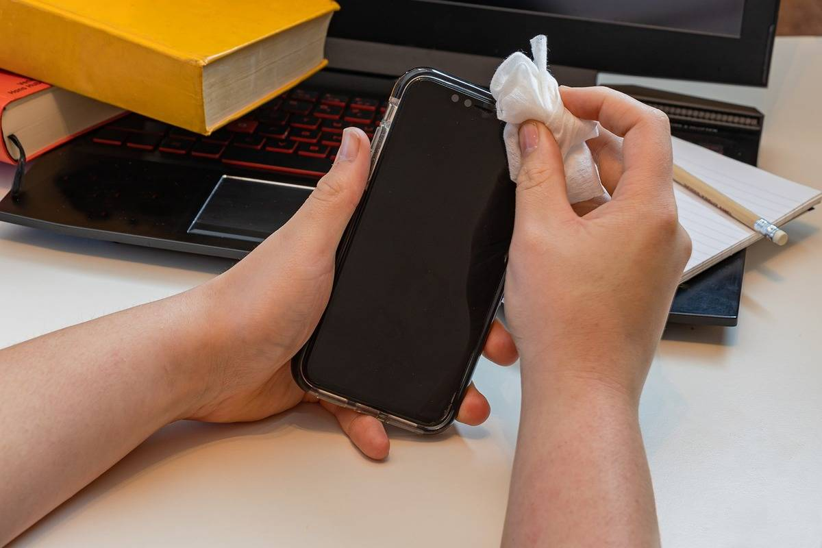 A person wipes down their smartphone.