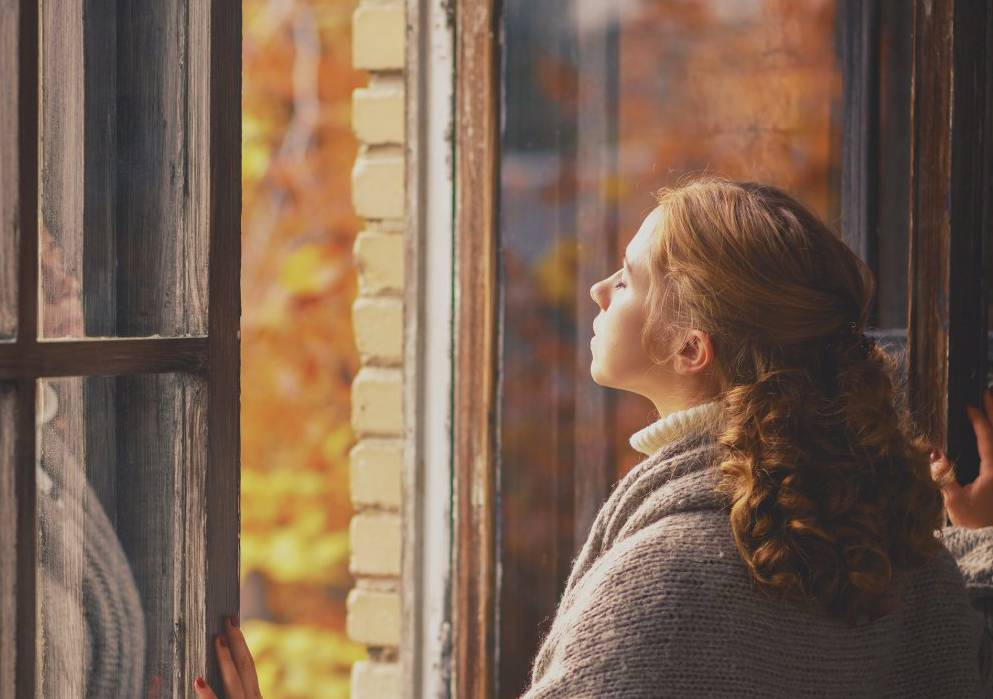 A woman smells the air after opening a window.