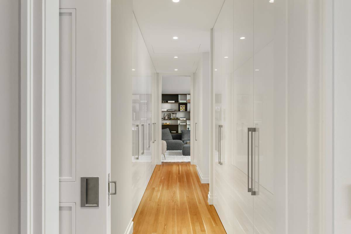 A thin hallway is lined with closets and bathrooms and leads to the media room.