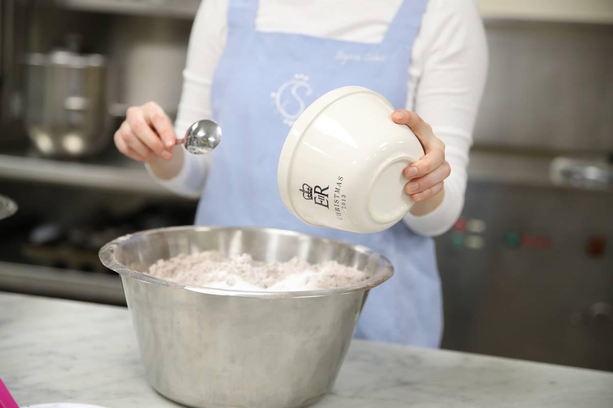 A baker pours flour into a bowel.