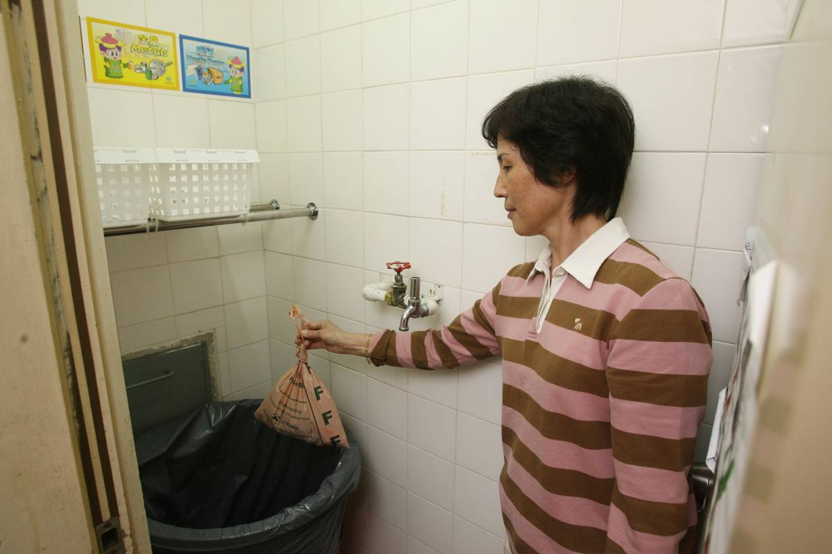 A woman throws away waste into her kitchen trash can.