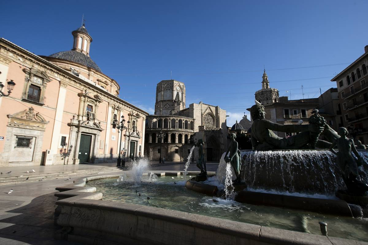 A city square in Valencia City features a fountain.