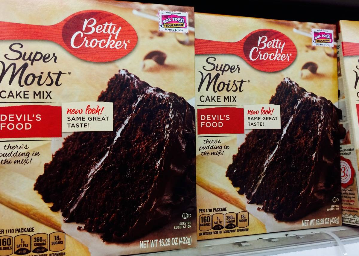 Boxes of Betty Crocker cake mix stand on a shelf.