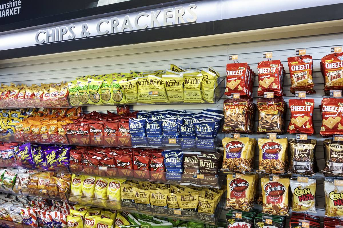 A chips and crackers aisle is on display at a convenience store.