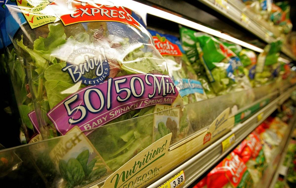 Bags of salad mix containing fresh spinach are seen on the shelf at a market.