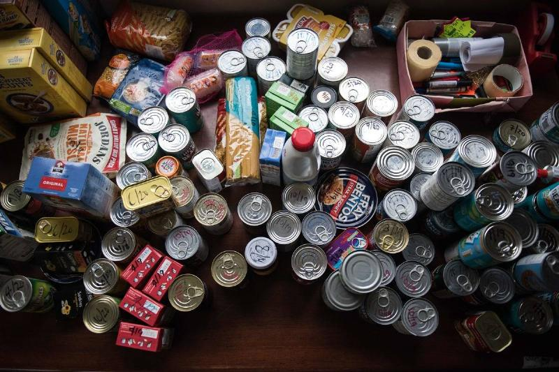 Parcels of canned food are stacked on the floor.