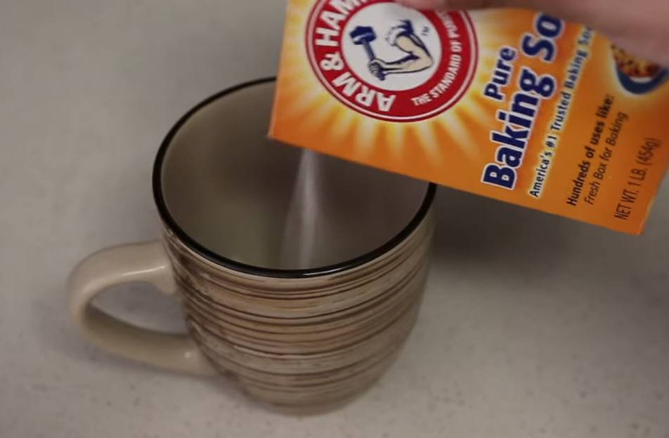 A YouTuber demonstrates how to remove coffee stains from a mug by pouring baking powder inside.