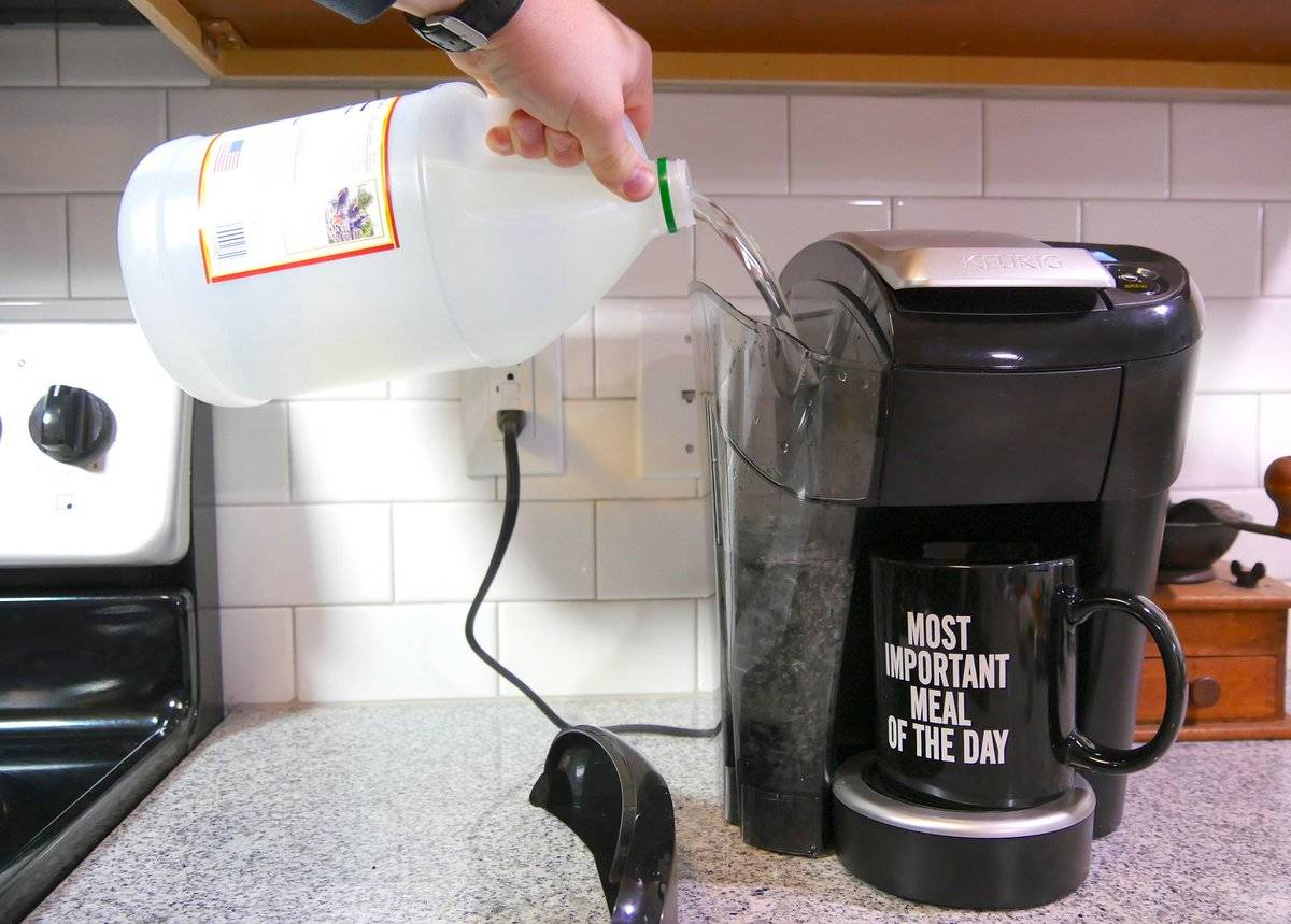 A person pours vinegar into a coffee maker to clean it.