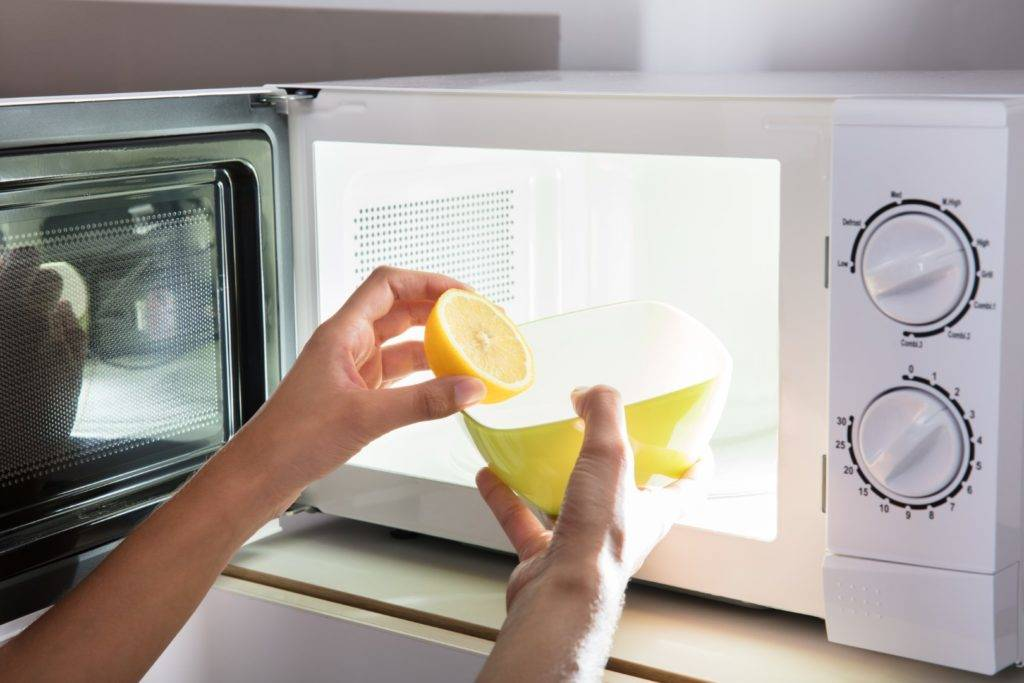 A person places a bowl of water and a lemon in a microwave.