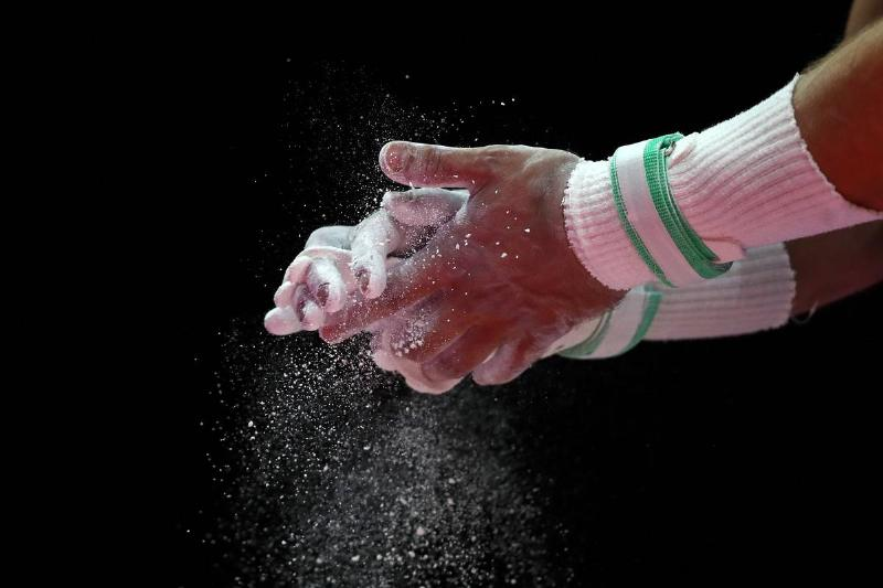 A gymnast dusts his hands with chalk.