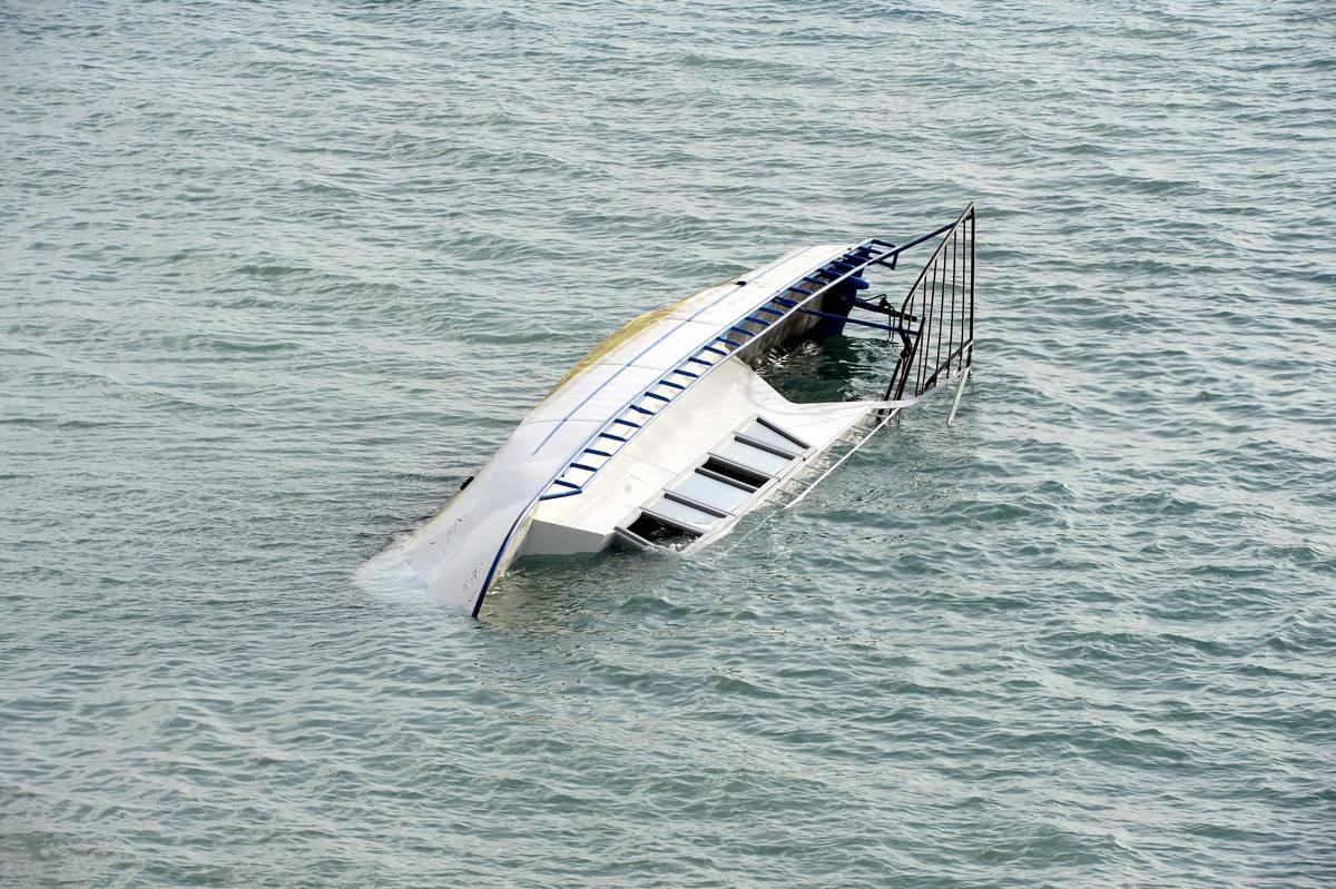 A capsized boat is half-sunk on its side in Lake Van.