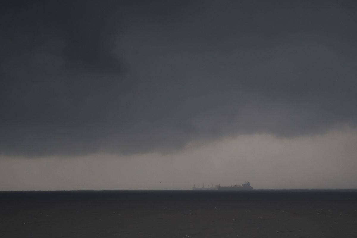 A dark storm is seen over the ocean horizon.