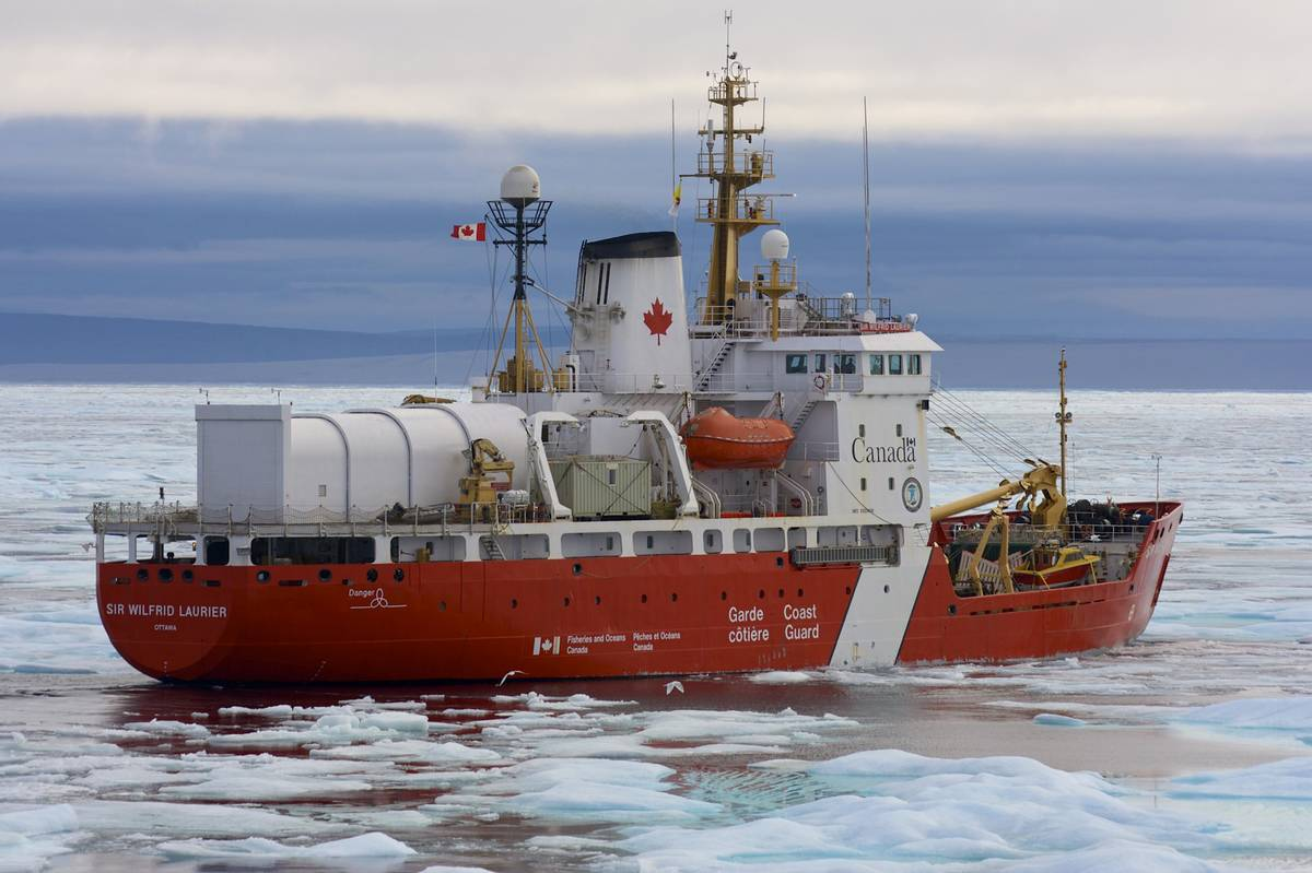 A Canadian Coast Guard Icebreaker sails through icy water.