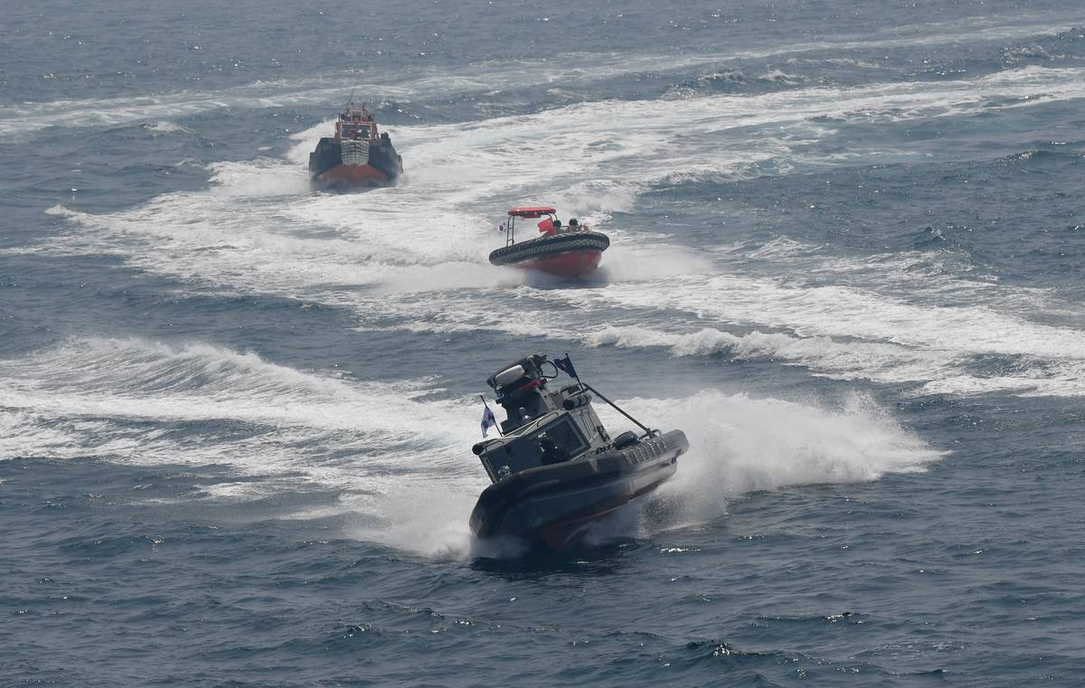 Coast guard patrol boats zig-zag across the sea.