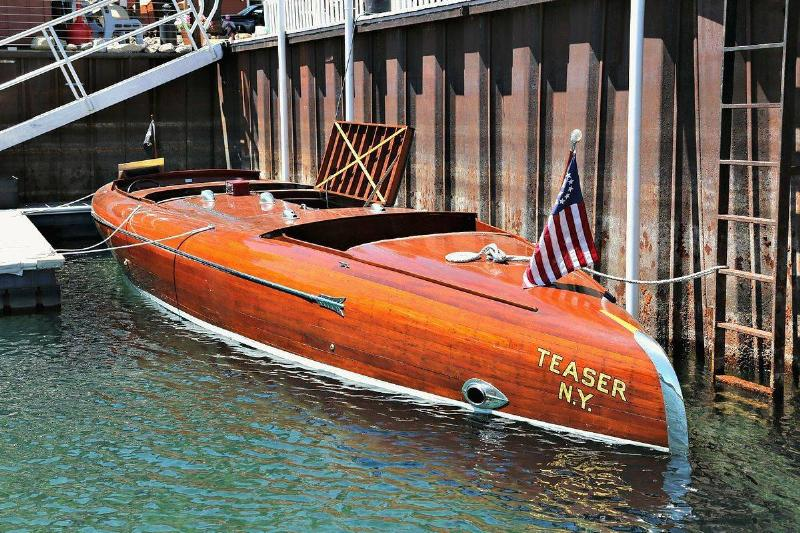 A wooden bootlegger boat is docked.