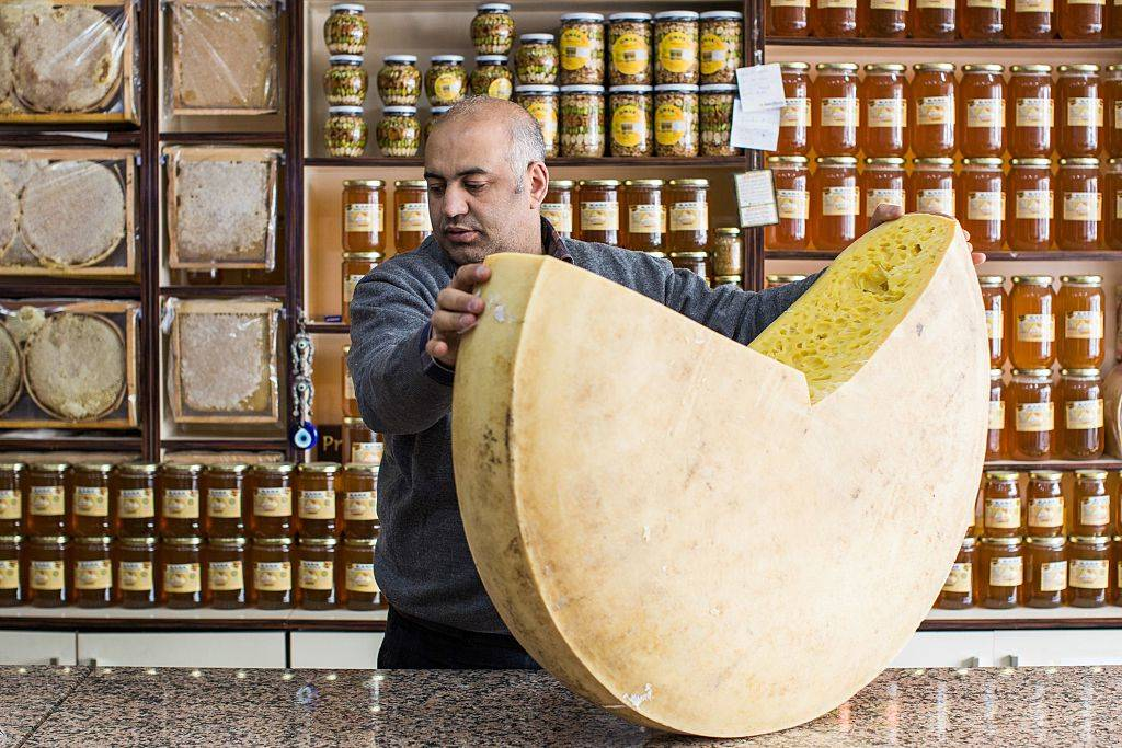 a man holding a giant cheese wheel