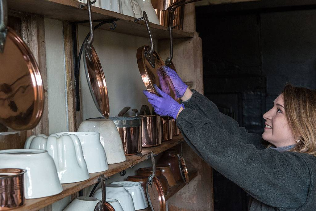 a woman cleaning a copper pan