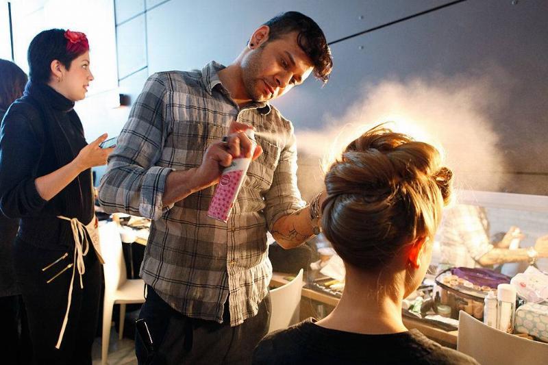 a man spraying dry shampoo on a blonde woman