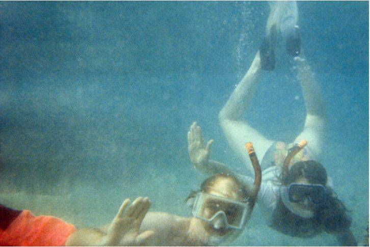 A family photo shows two kids scuba diving and waving at the camera.