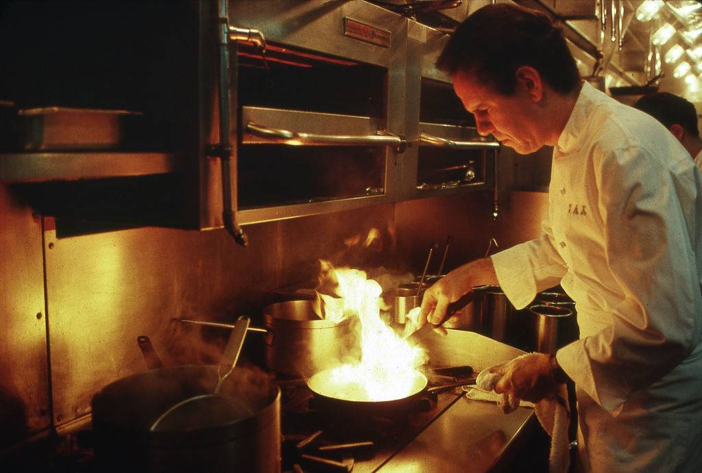 a chef cooking with fire over a stove