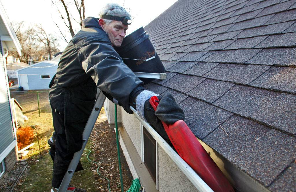 a man on a ladder cleaning the gutters on his roof