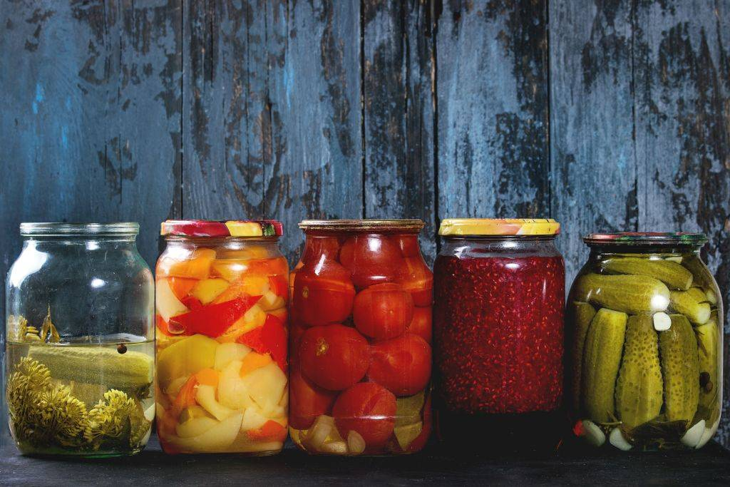 Variety glass jars of homemade pickled or fermented vegetables and jams in row with old dark blue wooden plank background