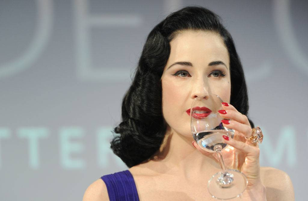 a woman with red lipstick drinking a glass of water