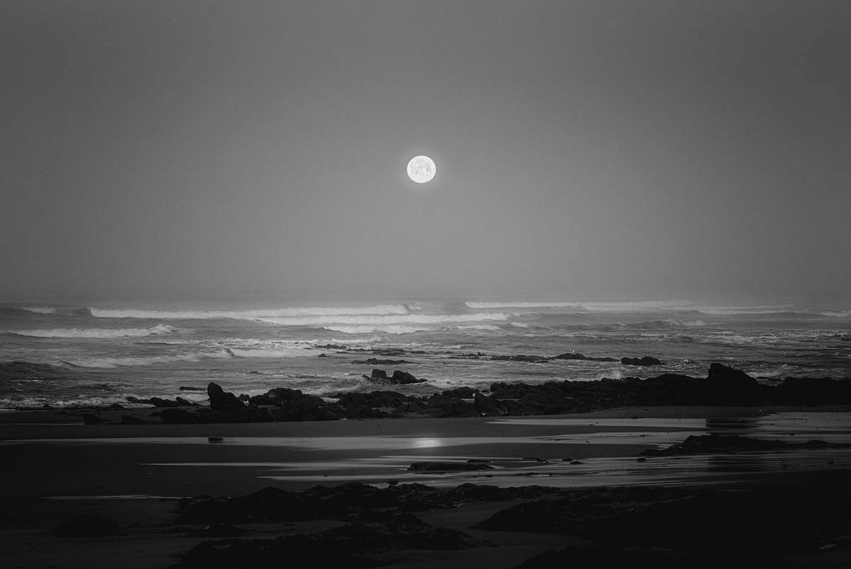 A full moon hovers over the ocean.