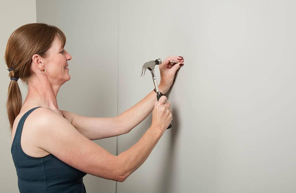 Woman using a hammer to bang a nail into a wall