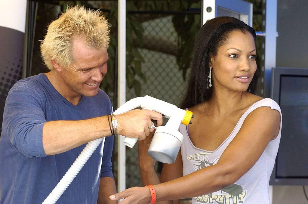 a woman getting a spray tan by a blonde man