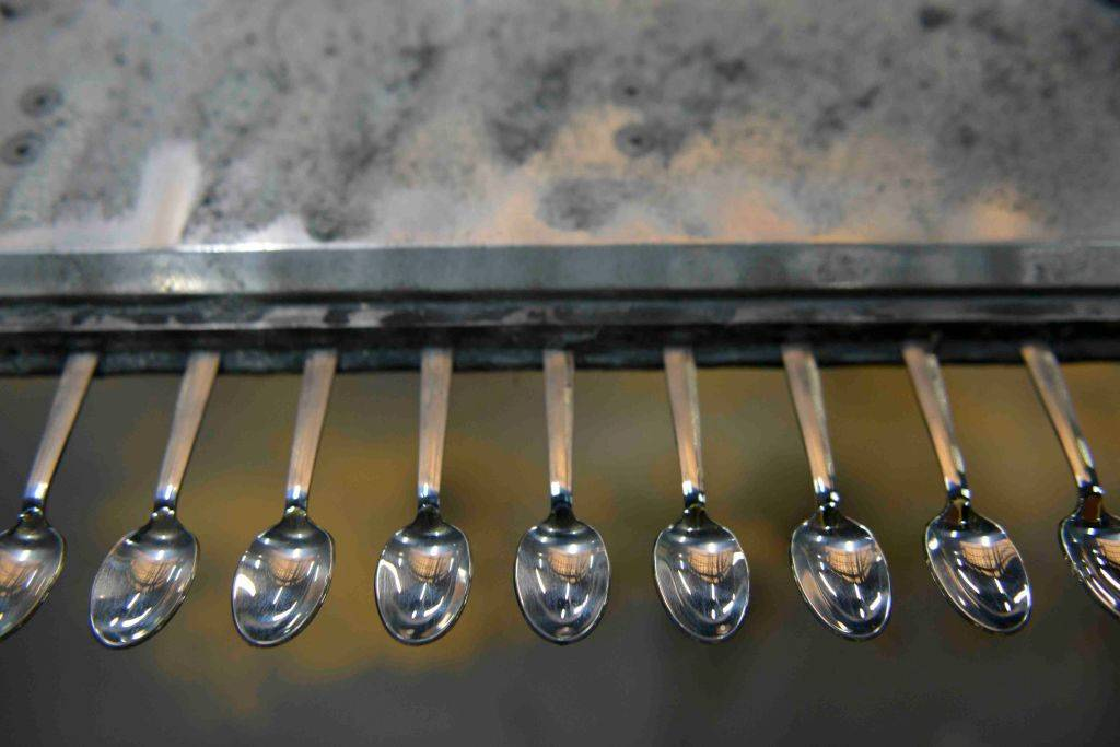 several metal spoons lined up on a counter