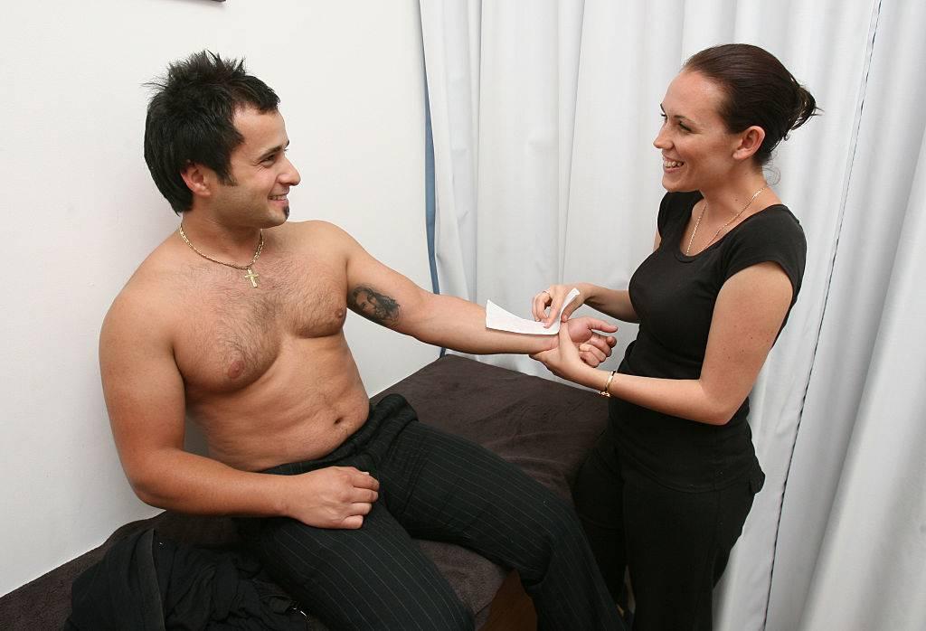 a woman waxing a man's arm