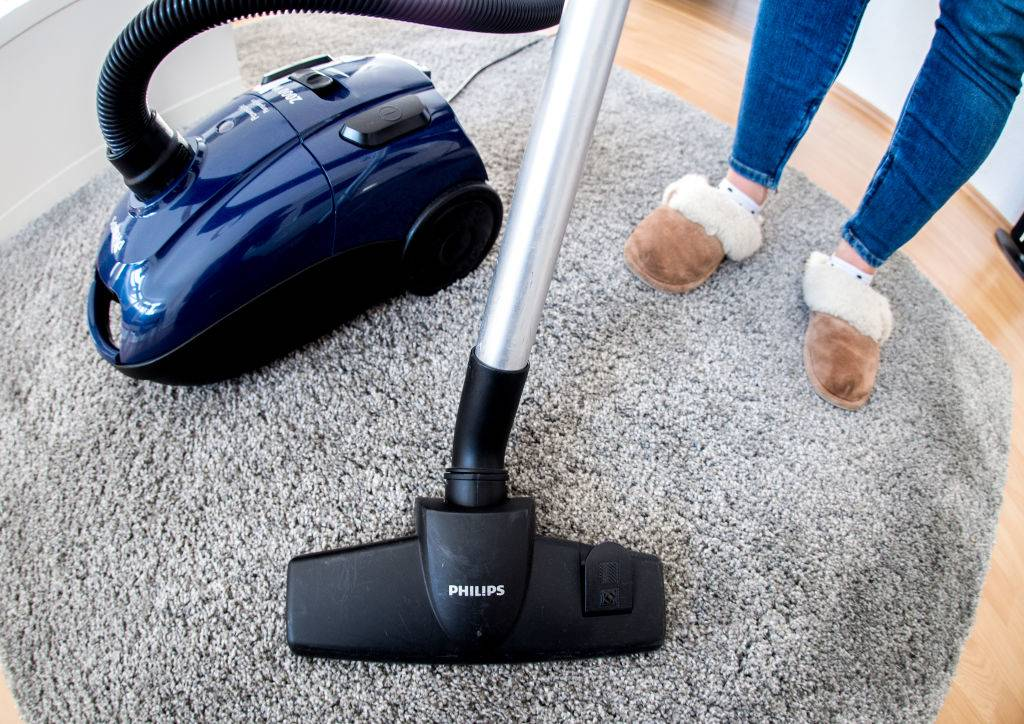 a woman with slippers vacuuming a carpet