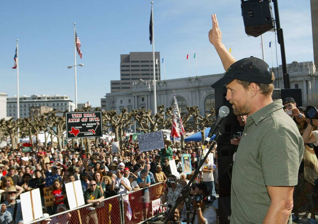 Actor Woody Harrelson flashes the peace sign to the crowd during an anti-war demonstration