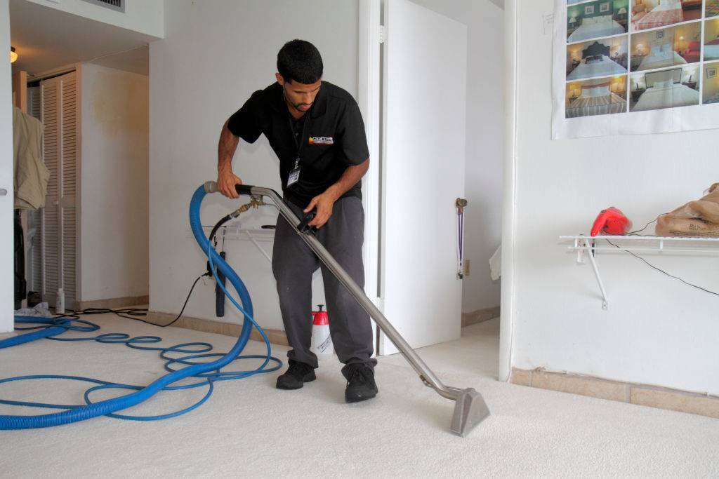 a man cleaning the carpets with a special vacuum