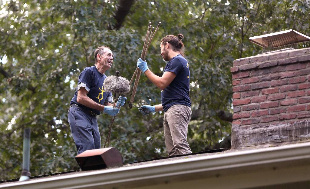 two men cleaning a chimney