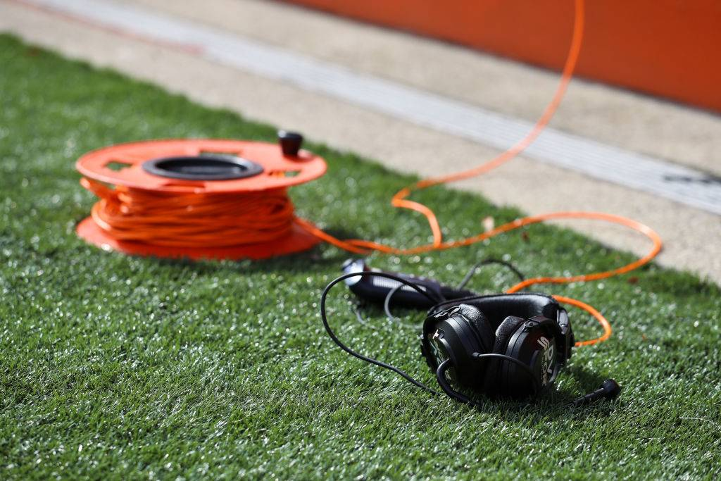 orange extension cord and headphones outside on the grass