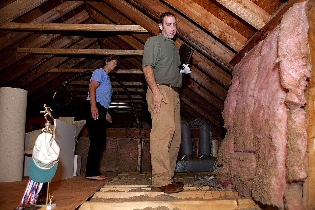 two people inspecting the insulation in an empty attic