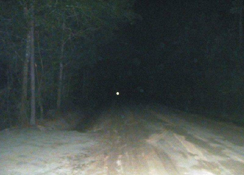 A mysterious light shines down Bragg Road at night.