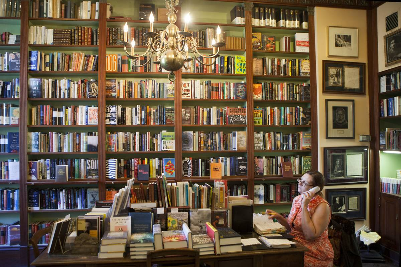 Bookshelves tower above the employees of Faulkner House Books.