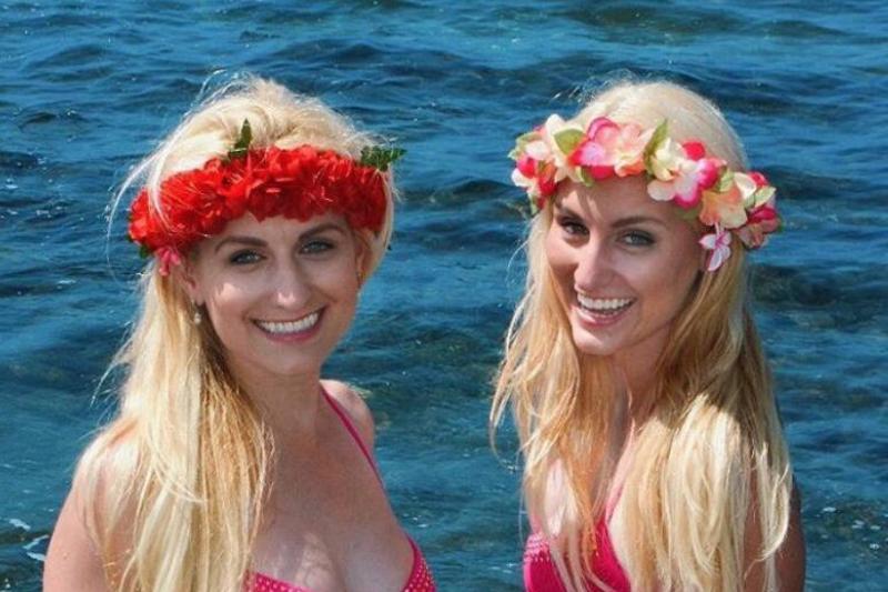 The Deane twins wear flower crowns in front of the ocean.