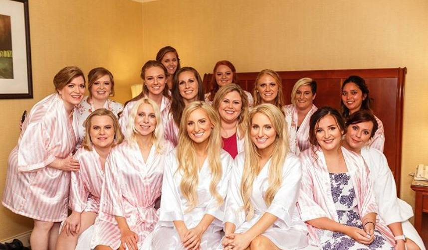 Brittany and Briana pose for a photo with their bridesmaids before their wedding.